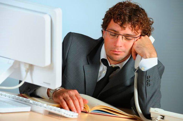 Сотрудник офиса спит за работой